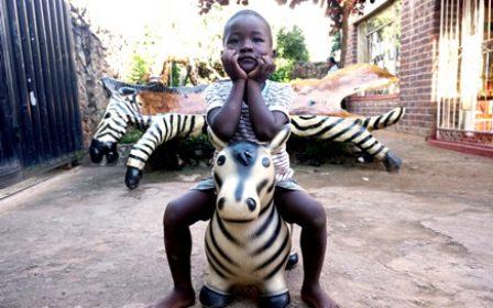 Junge sitzt auf einem Zebra